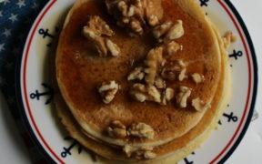 Ein Teller mit Pancakes, darüber Nüsse und Ahornsirup
